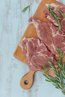 Surowe świeże mięso antrykot, rozmaryn i przyprawy na desce do krojenia.