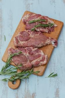 Surowe świeże mięso antrykot, rozmaryn i przyprawy na desce do krojenia