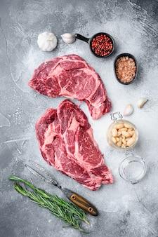 Surowe świeże mięso antrykot stek ribeye z mięsa black angus prime z zestawem składników, na szarym tle kamienia, widok z góry płasko leżał