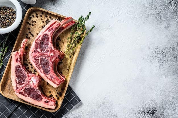 Surowe świeże mięso jagnięce na kościach z rozmarynem i przyprawami. szara powierzchnia. widok z góry. skopiuj miejsce