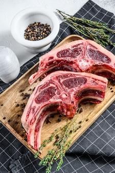 Surowe świeże mięso jagnięce na kościach z rozmarynem i przyprawami. szare tło. widok z góry