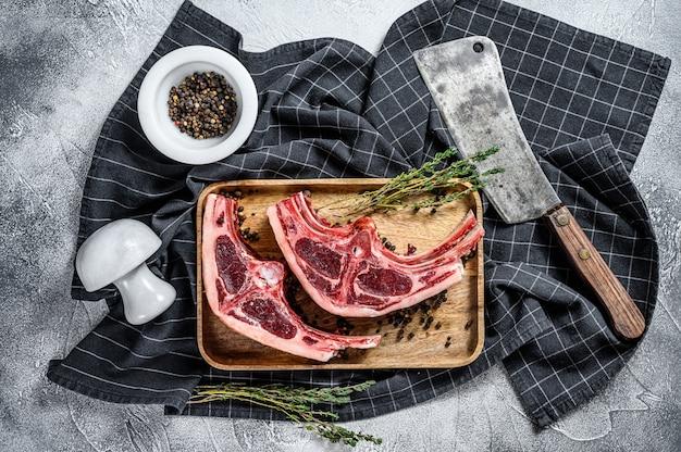 Surowe świeże mięso jagnięce na kościach z rozmarynem i przyprawami.