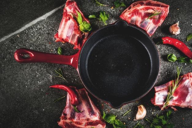 Surowe świeże mięso, niegotowane żeberka jagnięce lub wołowe z ostrą papryką, czosnkiem i przyprawami z patelnią do smażenia