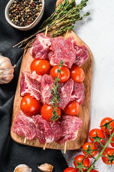 Surowe świeże mięso szaszłyk bbq z pomidorami i przyprawami