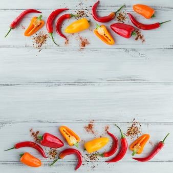 Surowe świeże organiczne czerwone papryczki chili i różne przyprawy na białym tle drewnianych