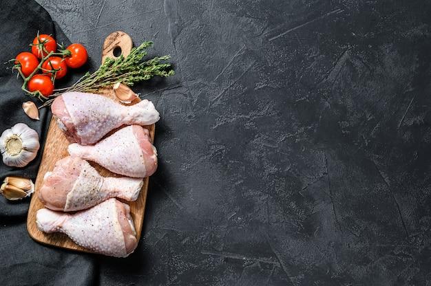 Surowe, świeże podudzia z kurczaka z przyprawami i warzywami na drewnianej desce do krojenia