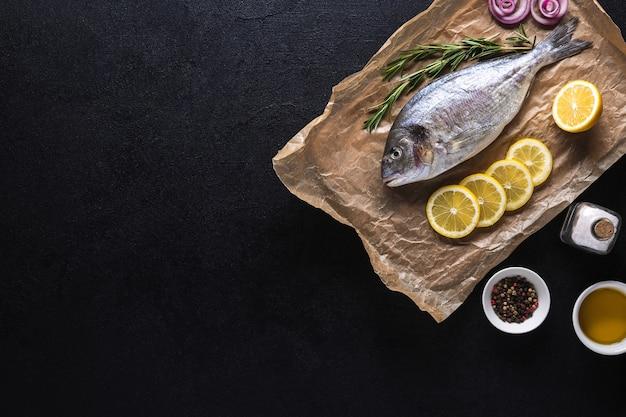 Surowe świeże ryby dorado na papierze do gotowania przygotowane do gotowania z przyprawami na czarnym tle. owoce morza. widok z góry. skopiuj miejsce.