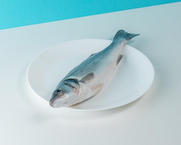 Surowe świeże ryby labraks na białym talerzu