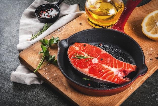 Surowe świeże ryby łosoś ze składnikami do gotowania oliwy z oliwek, cytryny, cebuli, natki pietruszki, rozmarynu, na patelni, stół z czarnego kamienia, copyspace