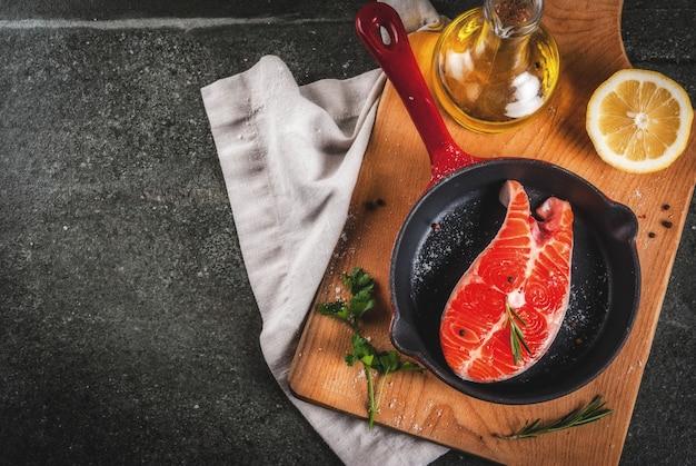 Surowe świeże ryby łosoś ze składnikami do gotowania oliwy z oliwek, cytryny, cebuli, natki pietruszki, rozmarynu, na patelni, stół z czarnego kamienia, widok z góry copyspace