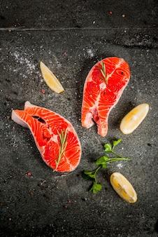 Surowe świeże ryby łosoś ze składnikami do gotowania oliwy z oliwek, cytryny, cebuli, natki pietruszki, rozmarynu, na stole z czarnego kamienia, widok z góry copyspace