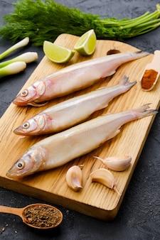 Surowe świeże ryby pachnące na drewnianej desce do krojenia z przyprawami i ziołami