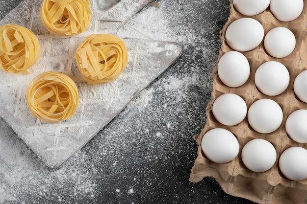 Surowe, świeże tagliatelle gniazduje z mąką na drewnianej desce i jajkami