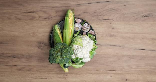 Surowe świeże warzywa na talerzu na drewnianym stole tło widok z góry.
