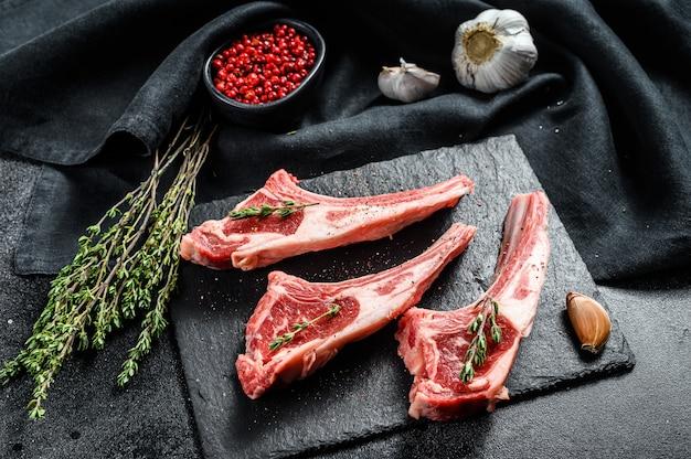 Surowe świeże żeberka jagnięce z pieprzem i rozmarynem. mięso ekologiczne. czarne tło. widok z góry