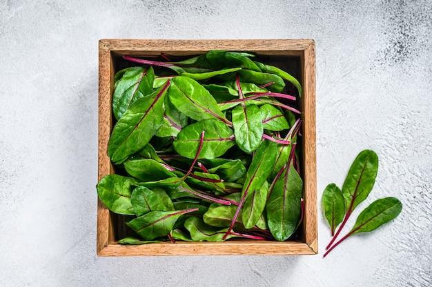 Surowe świeże zielone boćwina liści w drewnianym pudełku. białe tło. widok z góry.
