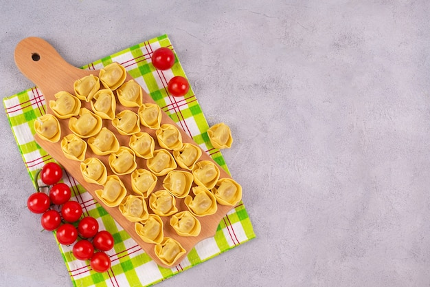Surowe tortelloni z nadzieniem grzybowym na drewnianej desce