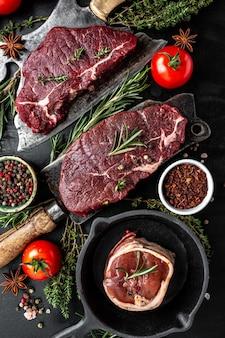 Surowe trzy steki wołowe na nóż rzeźnika mięsa z przypraw ciemnym tle. zamknij się pionowy obraz, miejsce na tekst.