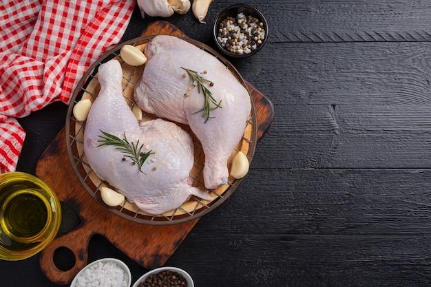 Surowe udka z kurczaka na ciemnej drewnianej powierzchni.