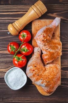 Surowe udka z kurczaka na desce do krojenia na drewnianym stole