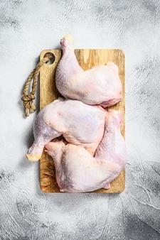 Surowe udka z kurczaka na desce do krojenia. szare tło.