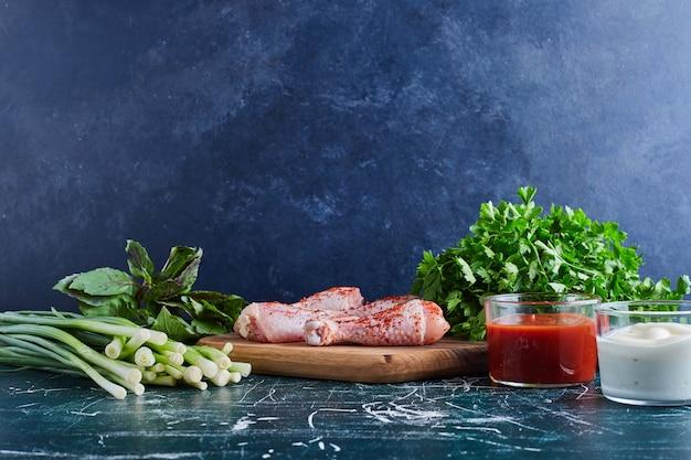 Surowe udka z kurczaka na drewnianym talerzu z ziołami dookoła.