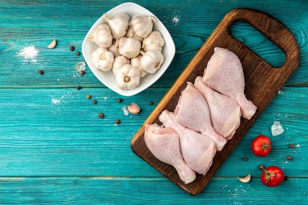 Surowe udka z kurczaka na niebieskiej powierzchni drewnianych