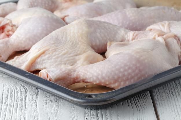 Surowe udka z kurczaka z bliska na tacy