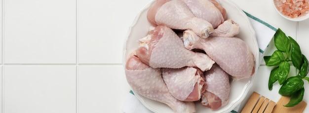 Surowe udka z kurczaka z liśćmi bazylii