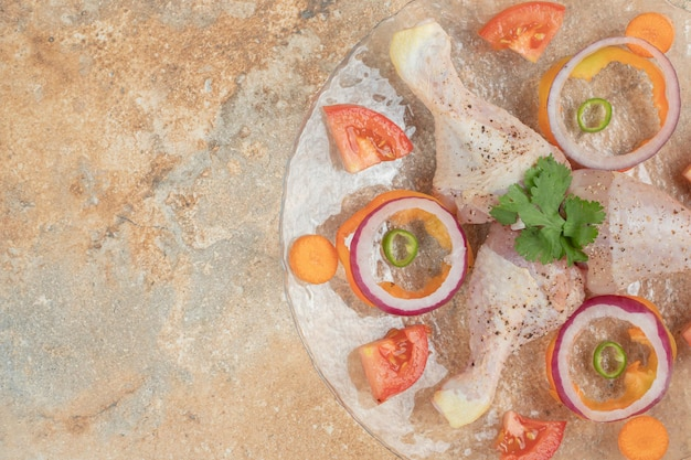 Surowe Udka Z Kurczaka Z Plastrami Pomidora I Cebuli Na Szklanym Talerzu Darmowe Zdjęcia