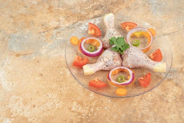 Surowe udka z kurczaka z plastrami pomidora i cebuli na szklanym talerzu