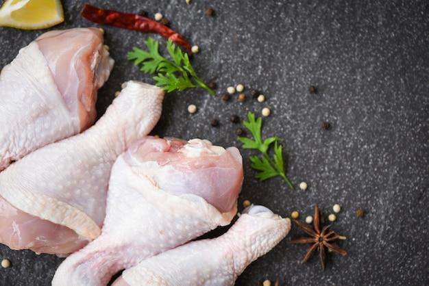 Surowe udka z kurczaka z ziołami chili i przyprawami cytrynowymi i grzybami na czarnej tablicy widok z góry, surowe niegotowane mięso z kurczaka marynowane ze składnikami do gotowania