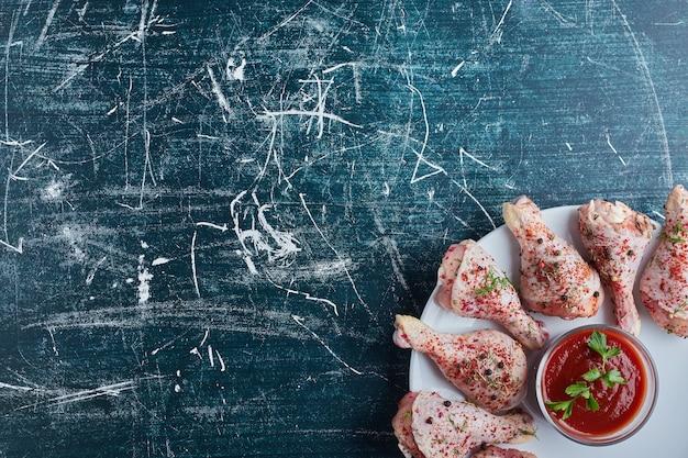 Surowe udka z kurczaka z ziołami i przyprawami oraz filiżanką keczupu.