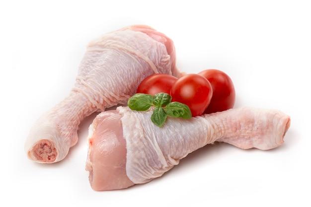 Surowe udka z kurczaka ze skórą ozdobione pomidorami i bazylią na białym tle.