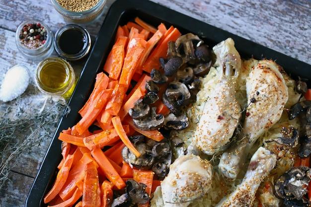 Surowe udka z warzywami i grzybami na blasze do pieczenia przed pieczeniem.