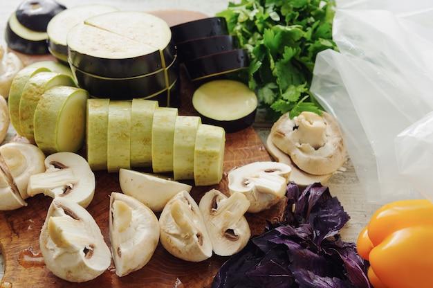 Surowe warzywa i grzyby w pobliżu opakowania próżniowego. kuchnia sous-vide, nowa technologia.