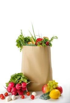 Surowe warzywa i owoce w bawełnianej torbie, na białym tle. organiczne jedzenie wegetariańskie, produkty spożywcze, koncepcja zdrowego stylu życia