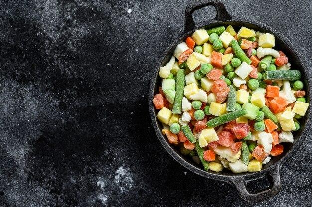 Surowe warzywa mrożone na patelni. wegetarianizm. czarne tło.