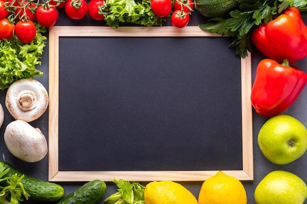 Surowe warzywa organiczne z czarną tablicą.