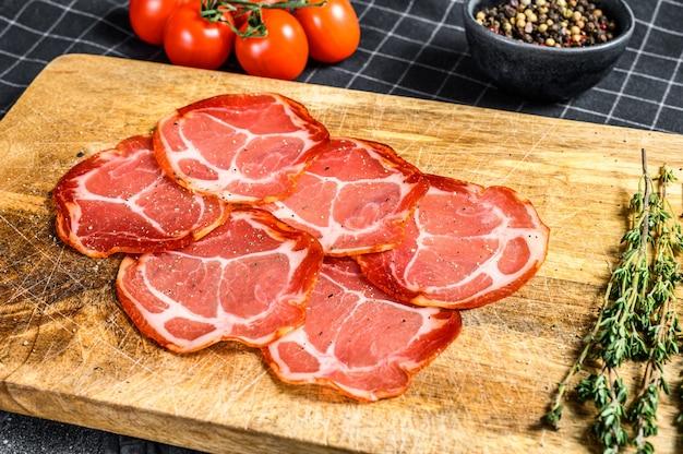 Surowe wędzone mięso jamon lomo. czarna powierzchnia. widok z góry