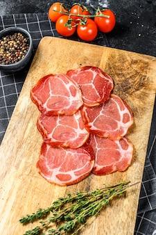 Surowe wędzone mięso jamon lomo. czarne tło. widok z góry