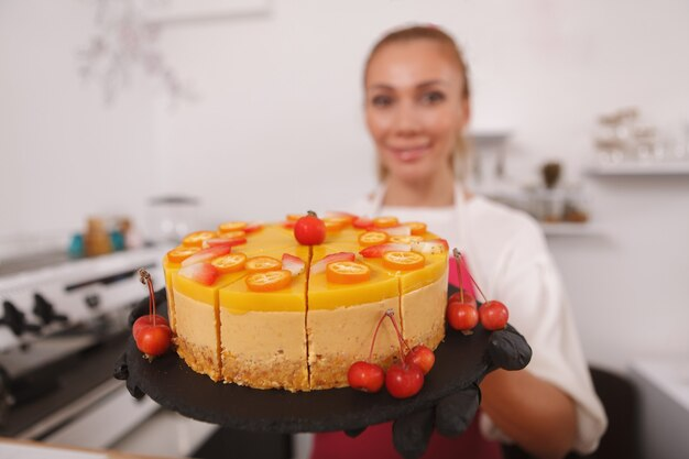 Surowe wegańskie ciasto mango kobieta cukiernik trzyma się do aparatu