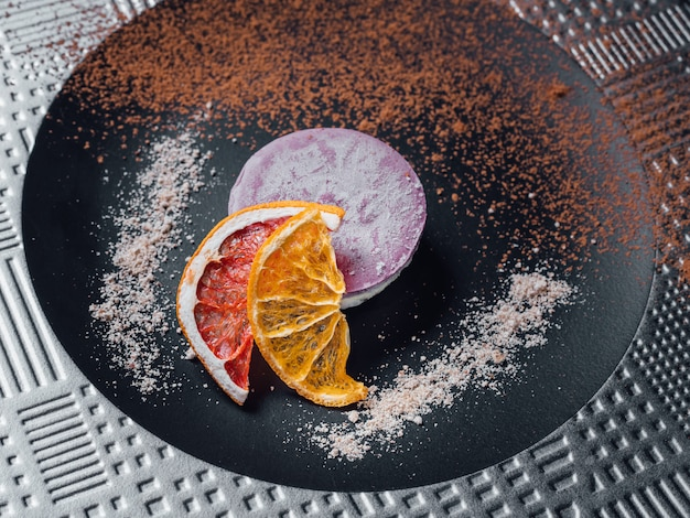 Surowe wegańskie ciasto z suszonych owoców, orzechów i kremowej kompozycji nerkowca, masła kokosowego, chleba świętojańskiego. na talerzu, odizolowywającym na czarnym tle, zamyka up