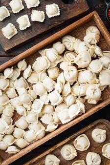 Surowe włoskie ravioli tortellini ze świeżym parmezanem i bazylią, pomidory na starym ciemnym drewnianym stole, widok z góry na płasko