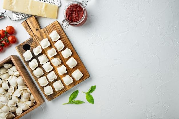 Surowe włoskie tortellini ravioli ze świeżym parmezanem i bazylią, pomidory na drewnianej desce, na białym tle, widok z góry na płasko, z copyspace i miejscem na tekst