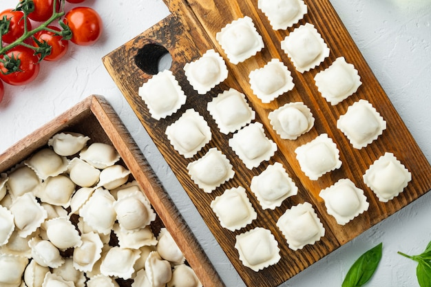 Surowe włoskie tortellini ravioli ze świeżym parmezanem i bazylią, pomidory na drewnianej desce, na białym tle, widok z góry na płasko