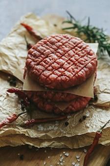 Surowe wołowe hamburgery z ziołami i przyprawami na ciemnym talerzu łupkowym