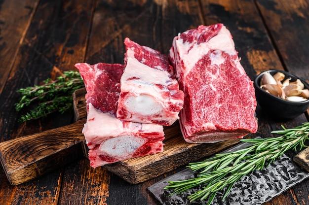 Surowe żeberka cielęce surowe mięso na deskę do krojenia rzeźnika z tasakiem. ciemne drewniane tło. widok z góry.