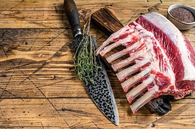 Surowe żeberka jagnięce na desce do krojenia z nożem. drewniane tła. widok z góry. skopiuj miejsce.