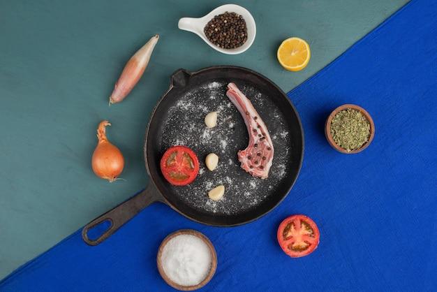 Surowe żeberka na czarnej patelni z warzywami i przyprawami na niebieskim stole.
